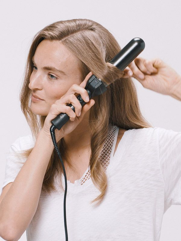 Styling soft waves with a curling iron.
