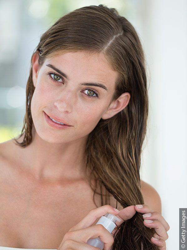 Mlada žena koja nanosi tretman bez ispiranja u spreju na svoju dugu, mokru, smeđu kosu