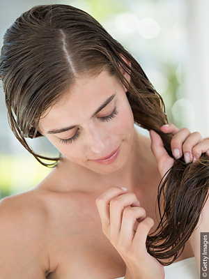 Woman with wet hair using a hair mask