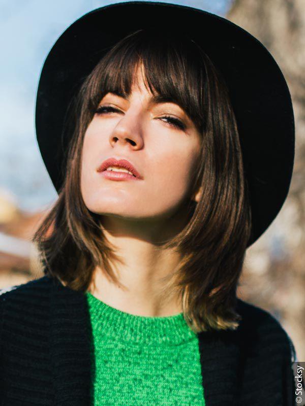 Smeđa žena sa dugim bobom koja nosi šiške poput zavese, sa crnim šeširom, zelenim topom i crno belim ispletenim džemperom.