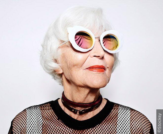 Older woman with white hair and stylish glasses.