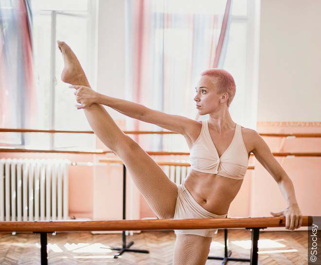 Woman doing a barre workout in a ballet studio.