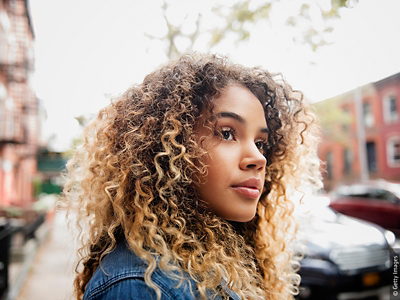 Woman with dark blonde curly hair