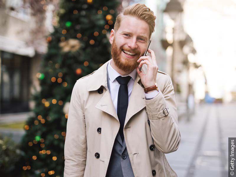 Elegancki mężczyzna rozmawiający przez telefon posiadający modną, zaczesana do tyłu męską fryzure.