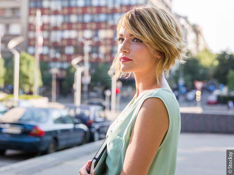Donna di profilo con caschetto asimmetrico biondo in abbigliamento elegante