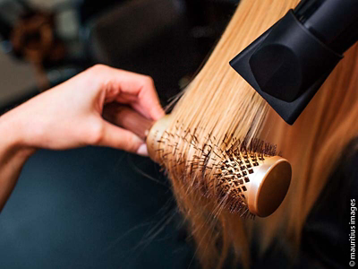 Hair being blow dried over a brush