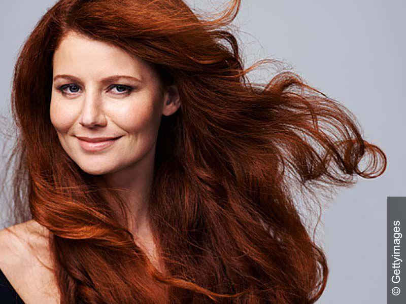 Frau mit roter Haarfarbe schaut freundlich in die Kamera