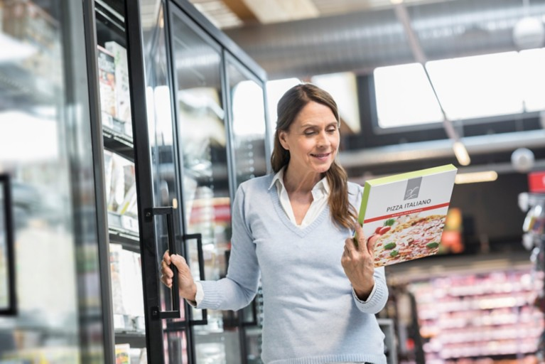 Woman looking at a box of frozen pizza