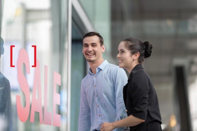 """一位女士和一位男士正激动地看向商店,商店窗口的红色海报上显示有""""促销""""的文字"""