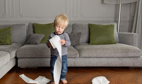 little boy standing in a living room in front of a sofa looking at a roll of toilet paper in his hands