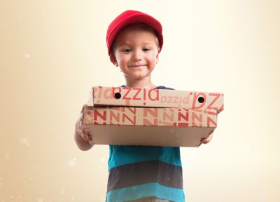 A boy in a red hat carries pizza boxes made of corrugated cardboard