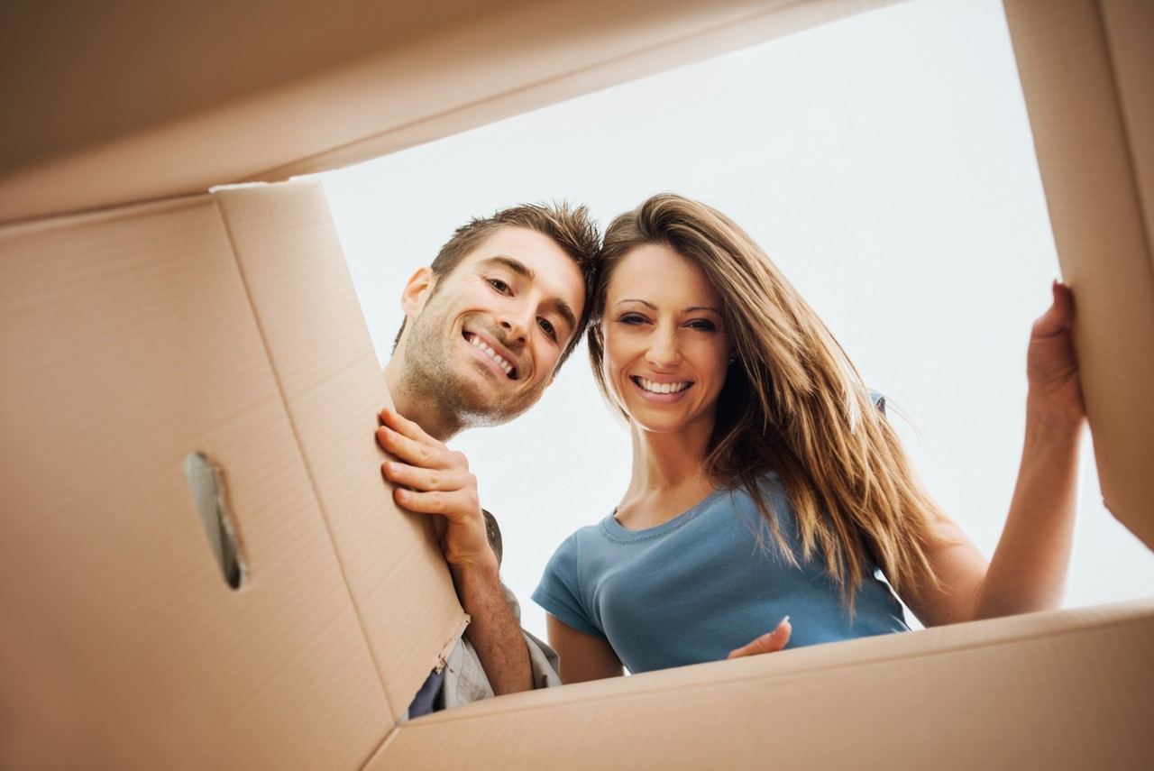 a young couple stare happily into an open corrugated cardboard box