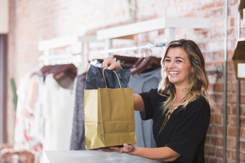 smiling woman working in a clothing store holding a paper bag in her hands