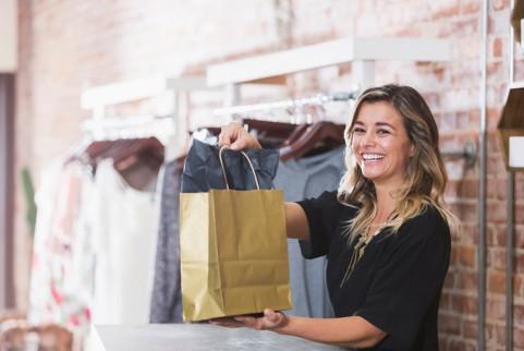 在服装店工作的微笑的女子,手中拿有一个纸袋。