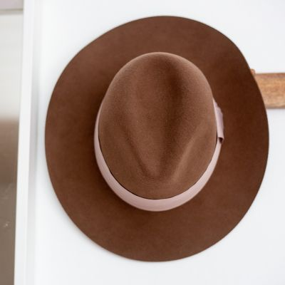 brown hat hanging on a white wall