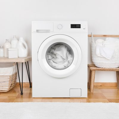 room with a running washing machine filled with white clothes nets to a laundry basket full of white clothes and several white cleaning products on top of a beige shelf