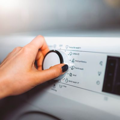 feminine hand with black polished nails setting up a washing machine program