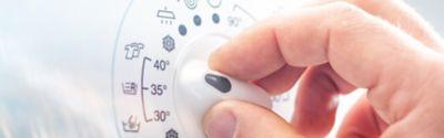 Nahaufnahme einer Männerhand, die an der Waschmaschine ein 40-Grad-Programm einstellt