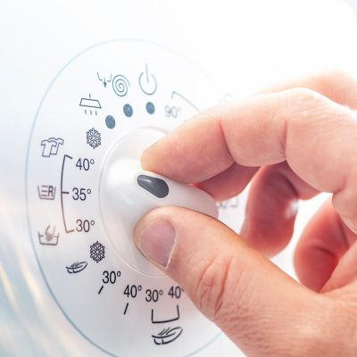 close-up of a masculine hand setting up the washing machine to the 40 degree program