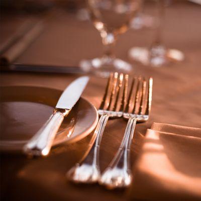 Zwei silberne Gabeln und ein silbernes Messer auf einer hellen Tischdecke