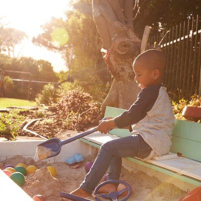 Kind spielt in einem Sandkasten voller Spielzeug