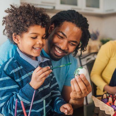 Vater und Sohn färben lachend in der Küche Ostereier