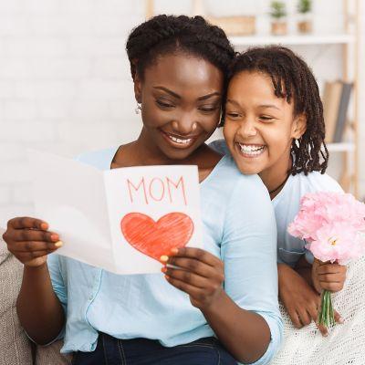 Mutter und Tochter betrachten lächelnd eine von der Tochter gebastelte Muttertagskarte