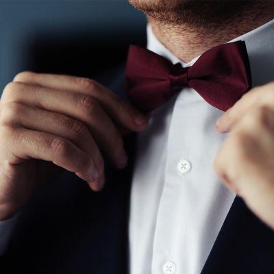 Mann im schwarzen Anzug und weißen Hemd richtet seine dunkelrote Fliege