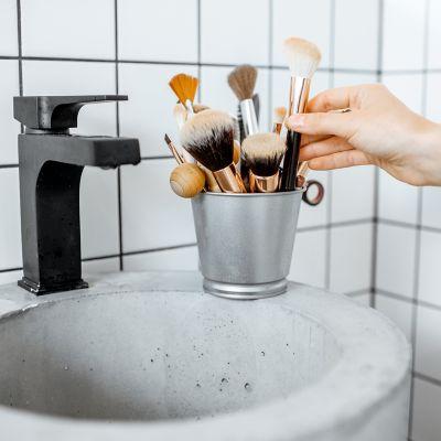 Grauer Behälter auf einem Waschbecken gefüllt mit verschiedenen Make-up-Pinseln, die gereinigt werden sollen