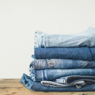 Fünf verschiedene Jeans liegen auf einem Holztisch