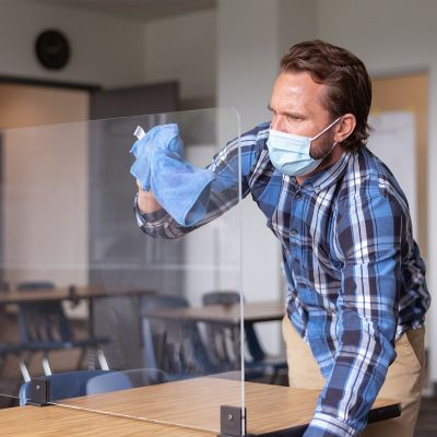 Mann mit Mundschutz und Handschuhen reinigt eine Scheibe zum Virenschutz aus Plexiglas, die die verschiedenen Tische in einem Klassenraum abtrennt