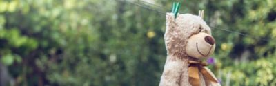 brown teddy bear with a brown bow hanging in the garden to get dry