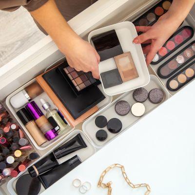 Mädchen, das verschiedene Bereiche für die Aufbewahrung von Make-up in einer großen weißen Schublade einrichtet