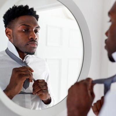 Ein junger Mann richtet sich seine stilvolle graue Krawatte auf einem weißen Hemd