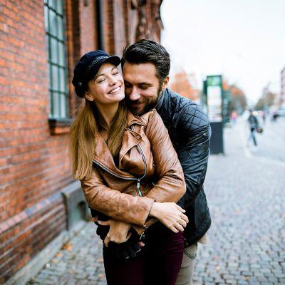 Ein junges Paar lächelt einander an, beide tragen eine Lederjacke