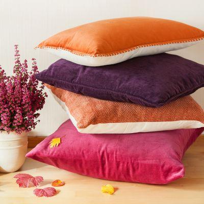 Vier bunte Kissen liegen gestapelt neben einer Pflanze mit rosa Blumen