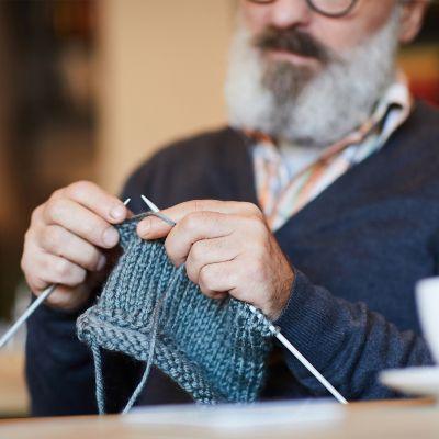 Mann mit langem grauen Bart und Brille strickt dunkelblaue Fäustlinge