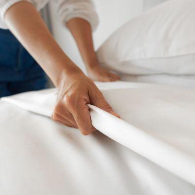 Frau bezieht Bett mit sauberen, weißen Laken