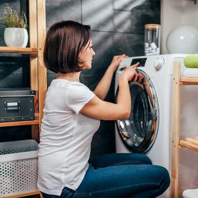 Kobieta w białej koszulce i dżinsach przegląda menu swojej pralki