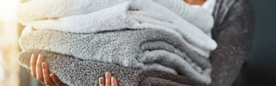 woman wearing a grey jacket holding 4 fresh grey and white towels