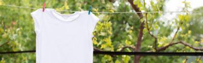 Ein weißes T-Shirt hängt draußen im Garten  zum Trocknen