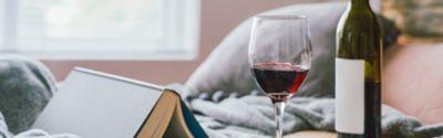 Geöffnete Flasche Rotwein neben einem Glas Wein auf einem Holzbrett.