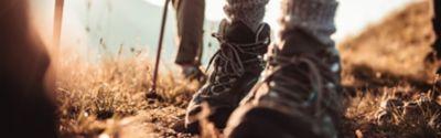 ZweiPersonen, die an einem sonnigen Ort wandern und Wanderkleidung und Wanderschuhe tragen