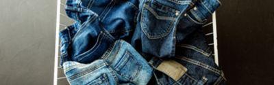 Weißer Korb mit 4schmutzigen Jeans darin
