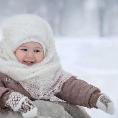 Baby mit weißen Fäustlingen und einem weißen Schal