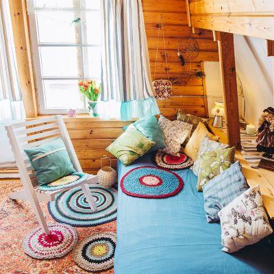 Bunte Kissen auf einem blauen Sofa und mehrere Flickenteppiche