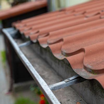 Schmutzige Regenrinne an rotem Dach