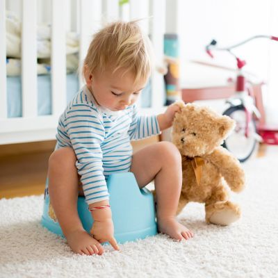Kleinkind spielt während des Töpfchentrainings mit seinem Teddybär