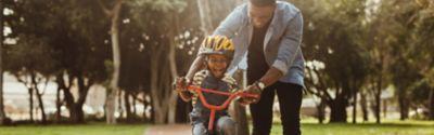 Vater bringt seinem Kind das Radfahren bei