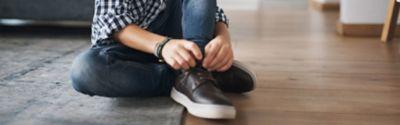 Ein Kind bindet seine Schnürsenkel zusammen